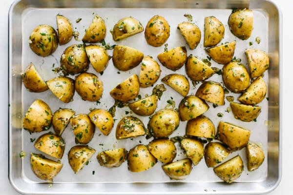 Cut potatoes spread out on a baking sheet.
