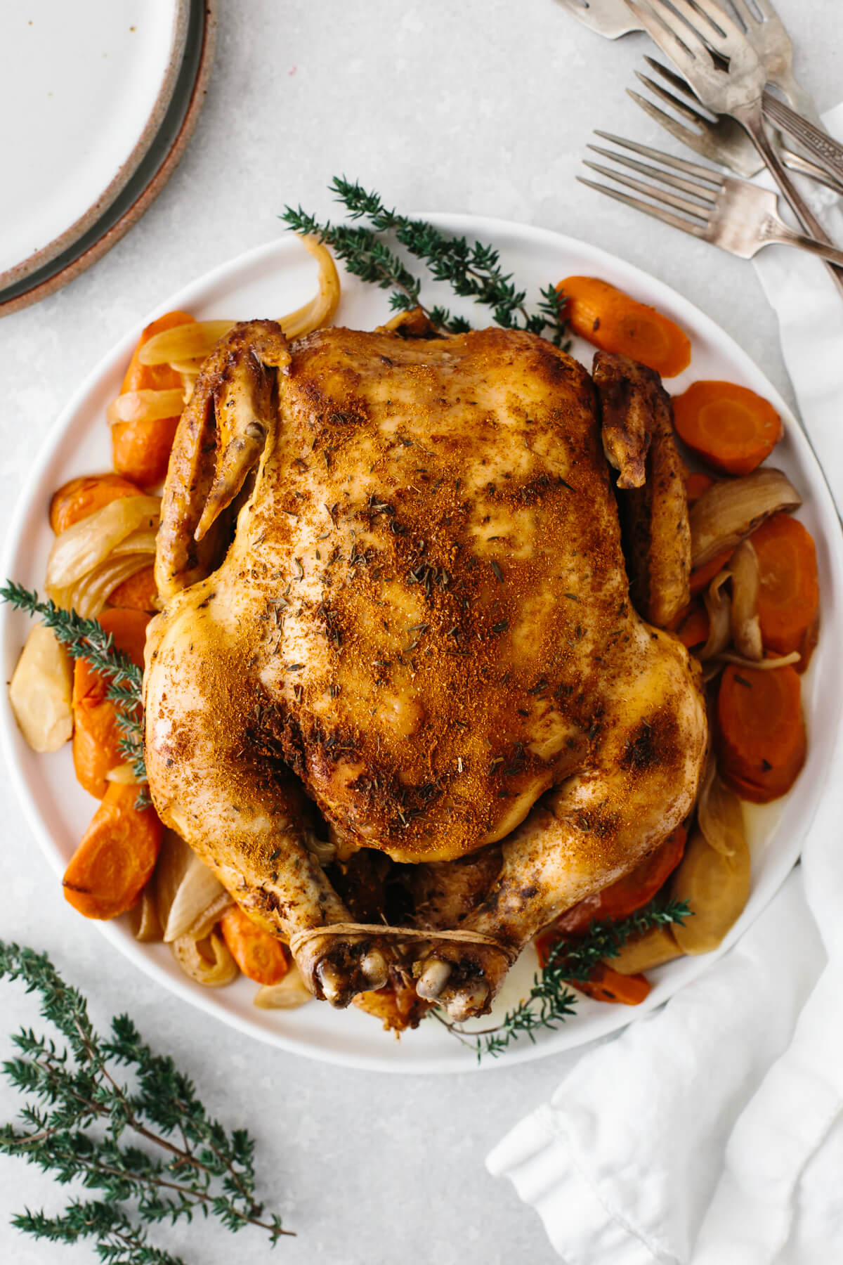 Slow cooker rotisserie chicken on a bed of vegetables on a plate.