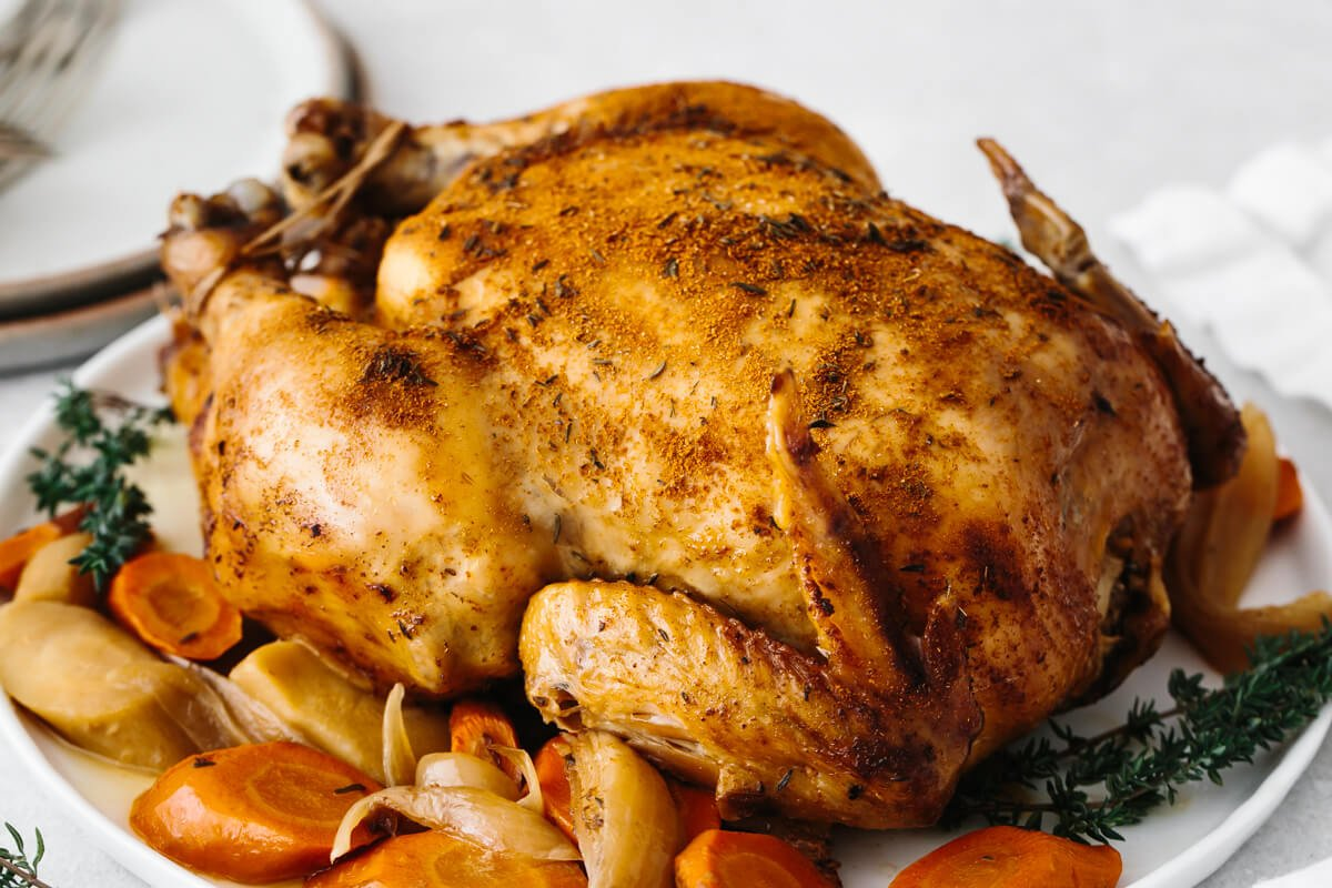 Slow cooker rotisserie chicken on a plate with vegetables.