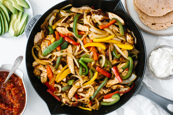 Serving the chicken fajitas with tortillas, guacamole and other ingredients.
