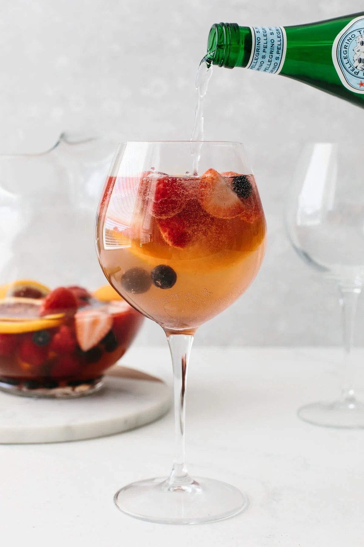 Sparkling water poured into Moscato Sangria.