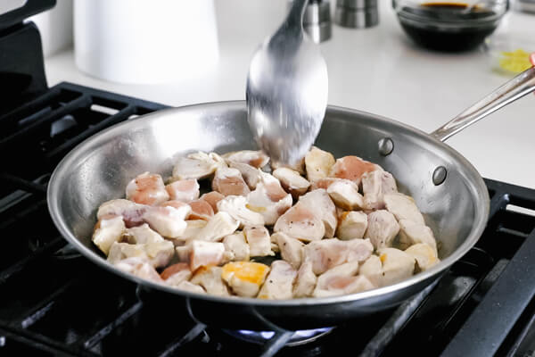 Cooking the other side of the diced chicken in a pan.