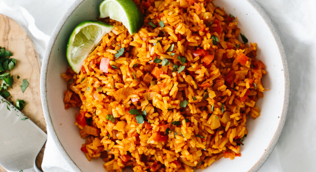 Mexican rice in a bowl with lime wedges.