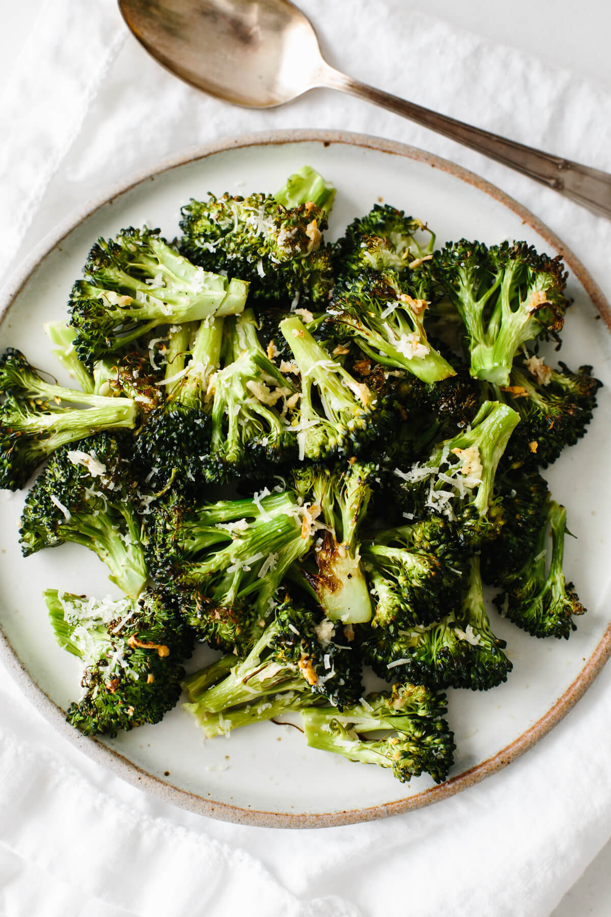 Roasted broccoli on a white plate.