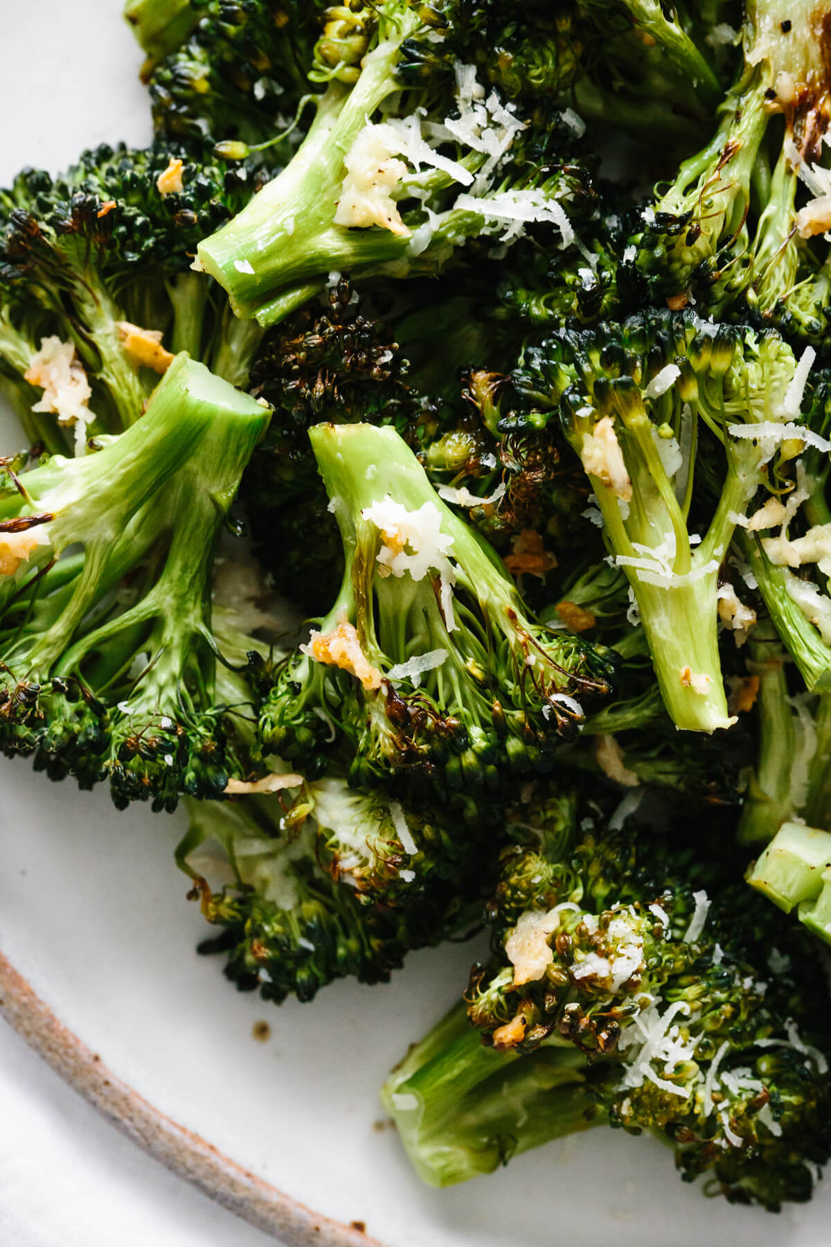Roasted broccoli piled on a plate.