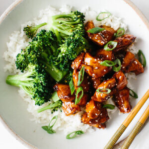 Teriyaki chicken in a bowl with rice and broccoli.