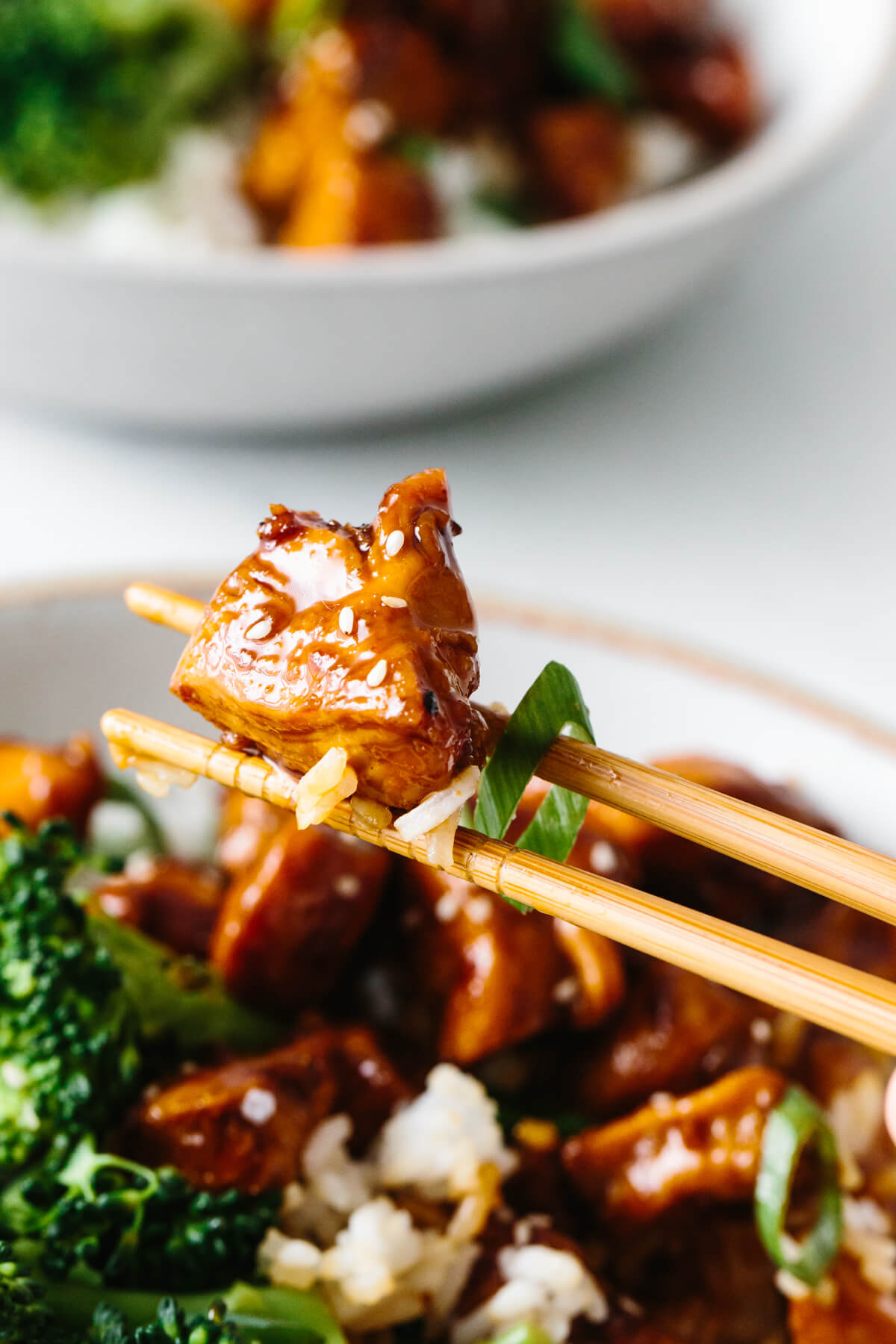 A piece of teriyaki chicken picked up with chopsticks.