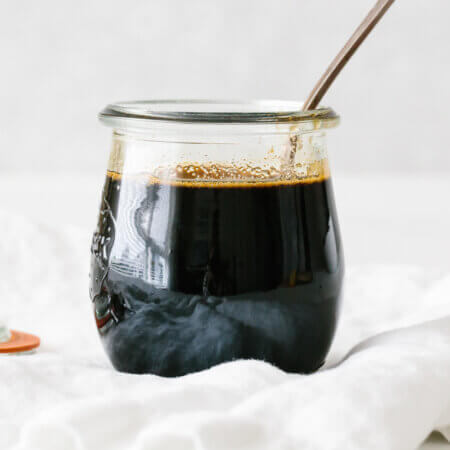 Teriyaki sauce in a glass jar with a spoon.
