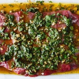 Carne asada marinade on top of steak.