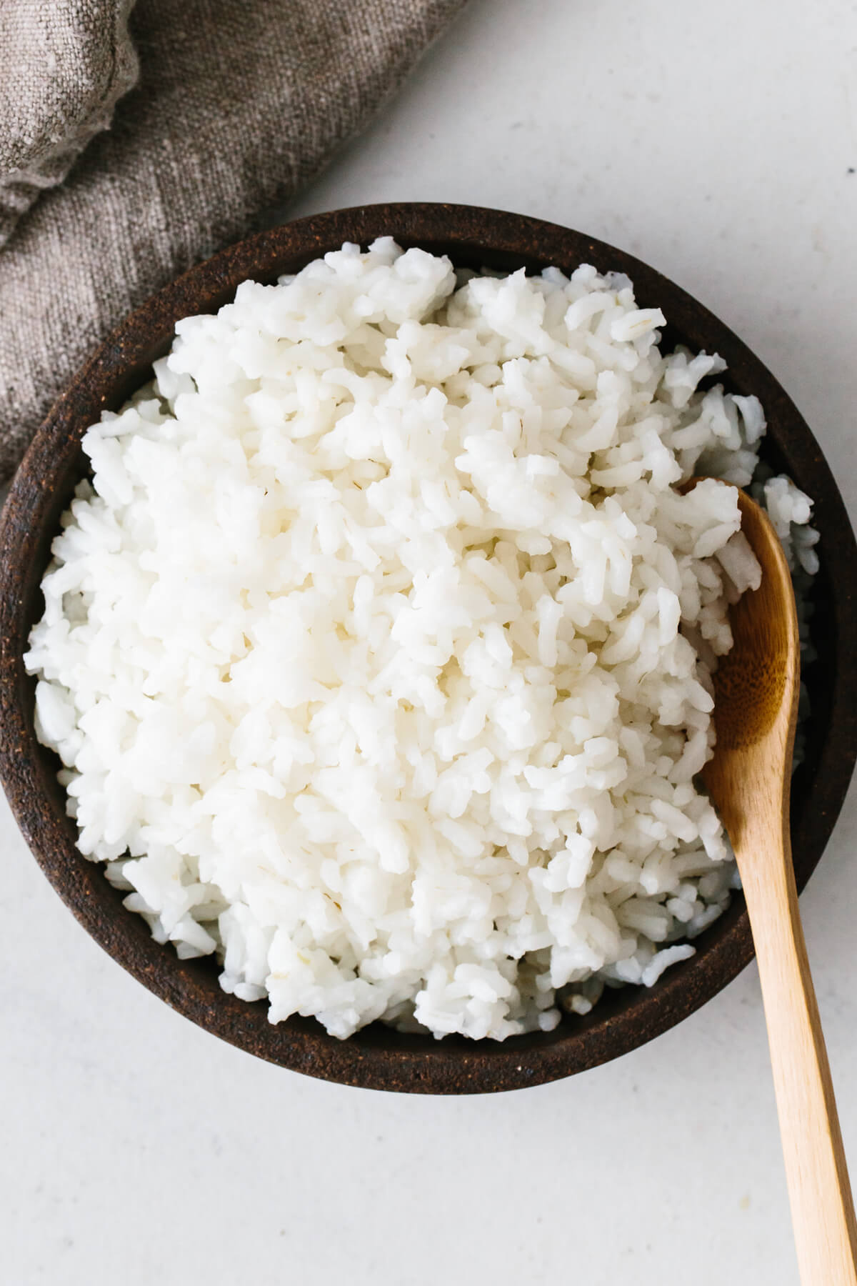 Cooked rice in a bowl with spoon.