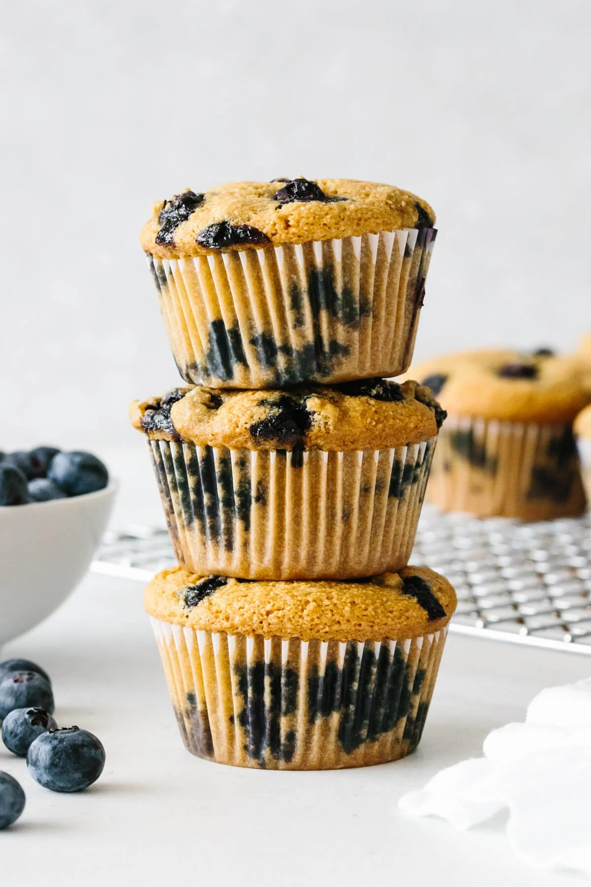 Three paleo blueberry muffins stacked on top of each other.