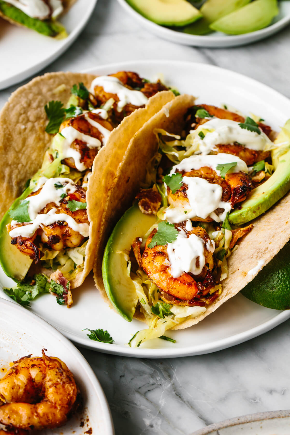 Shrimp tacos on a plate next to avocado