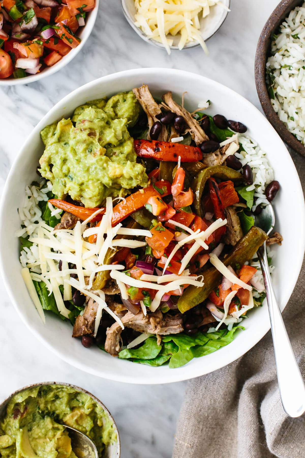 A carnitas burrito bowl, in a white bowl, surrounded by ingredients.