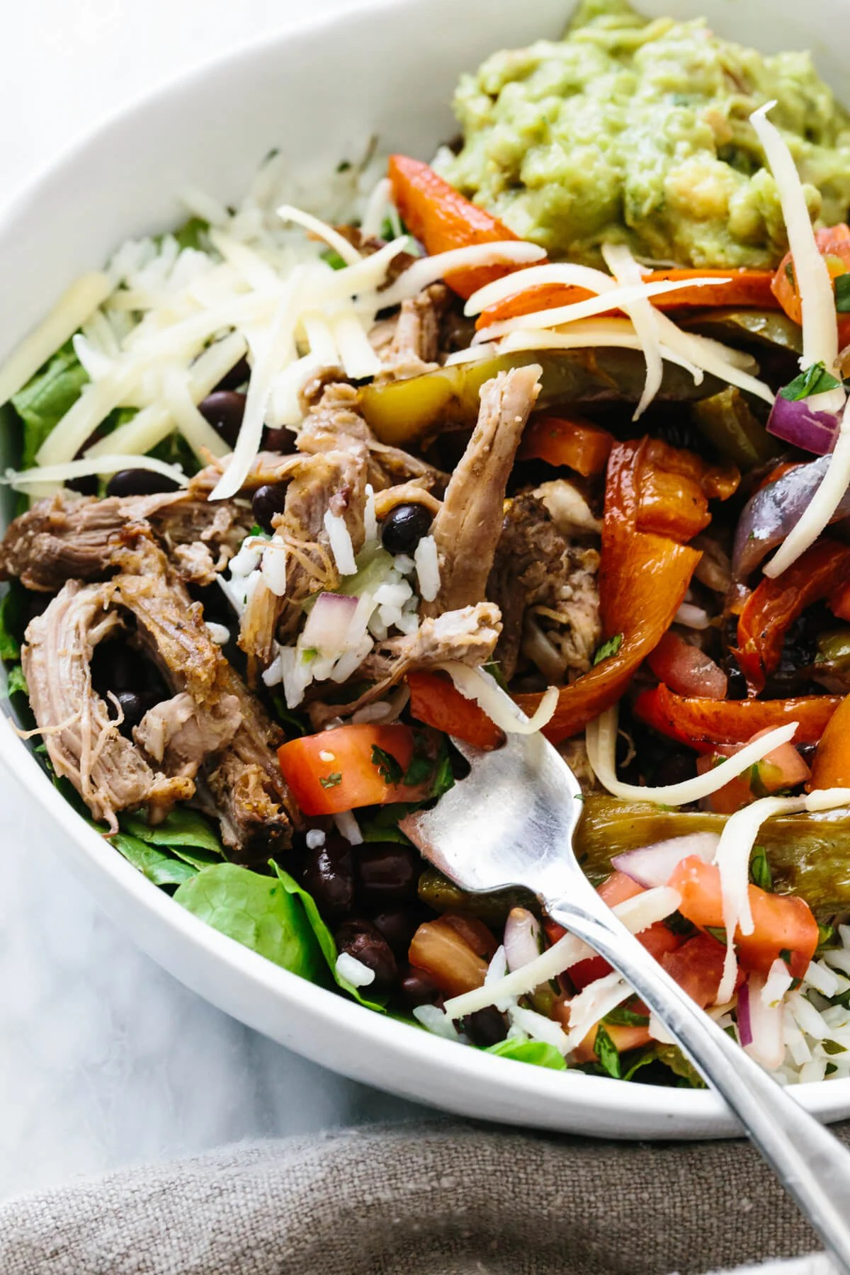 Up close shot of carnitas burrito bowl with a fork full of ingredients.