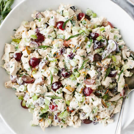 Chicken salad in a white bowl next to small bowls of diced celery, chopped parsley and fresh tarragon.