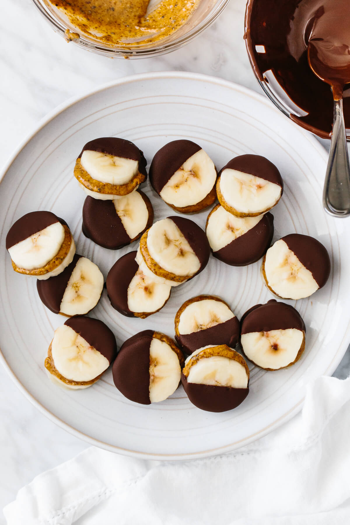 Frozen chocolate banana bites on a plate next to bowls of chocolate and almond butter.
