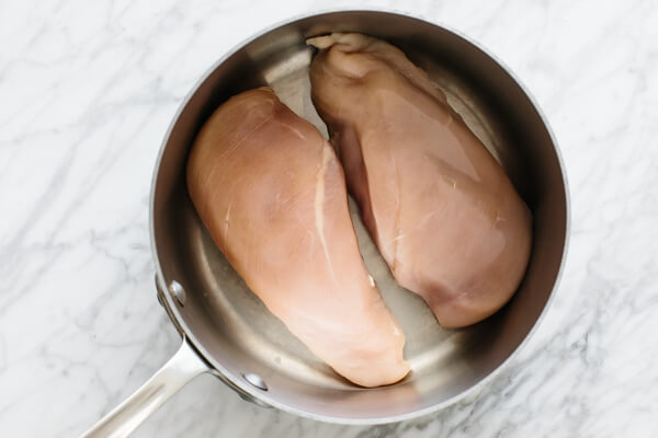 Two chicken breasts in a pot.