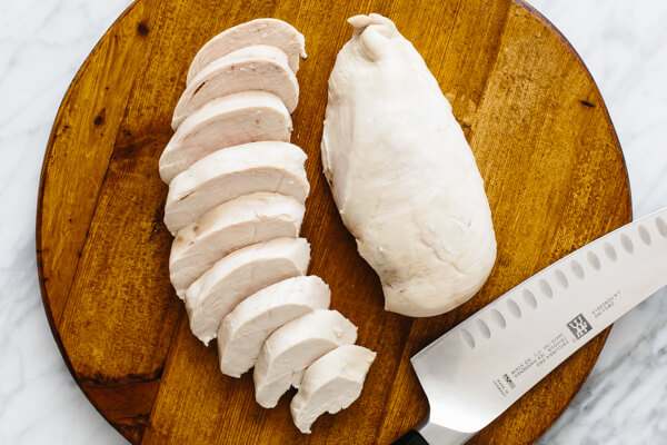 Poached chicken on a cutting board.