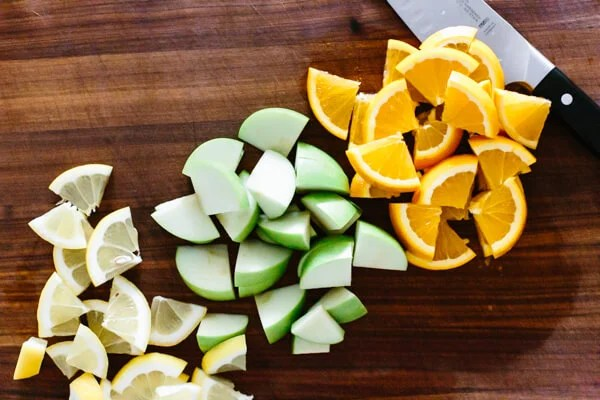 Chopping fruit for sangria on a cutting board.