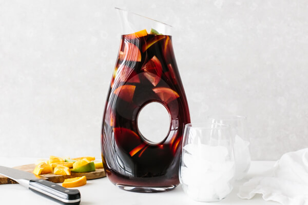 Adding sangria ingredients to a pitcher.