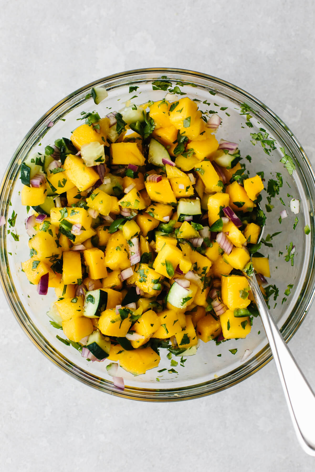 Mixing mango salsa in a bowl.