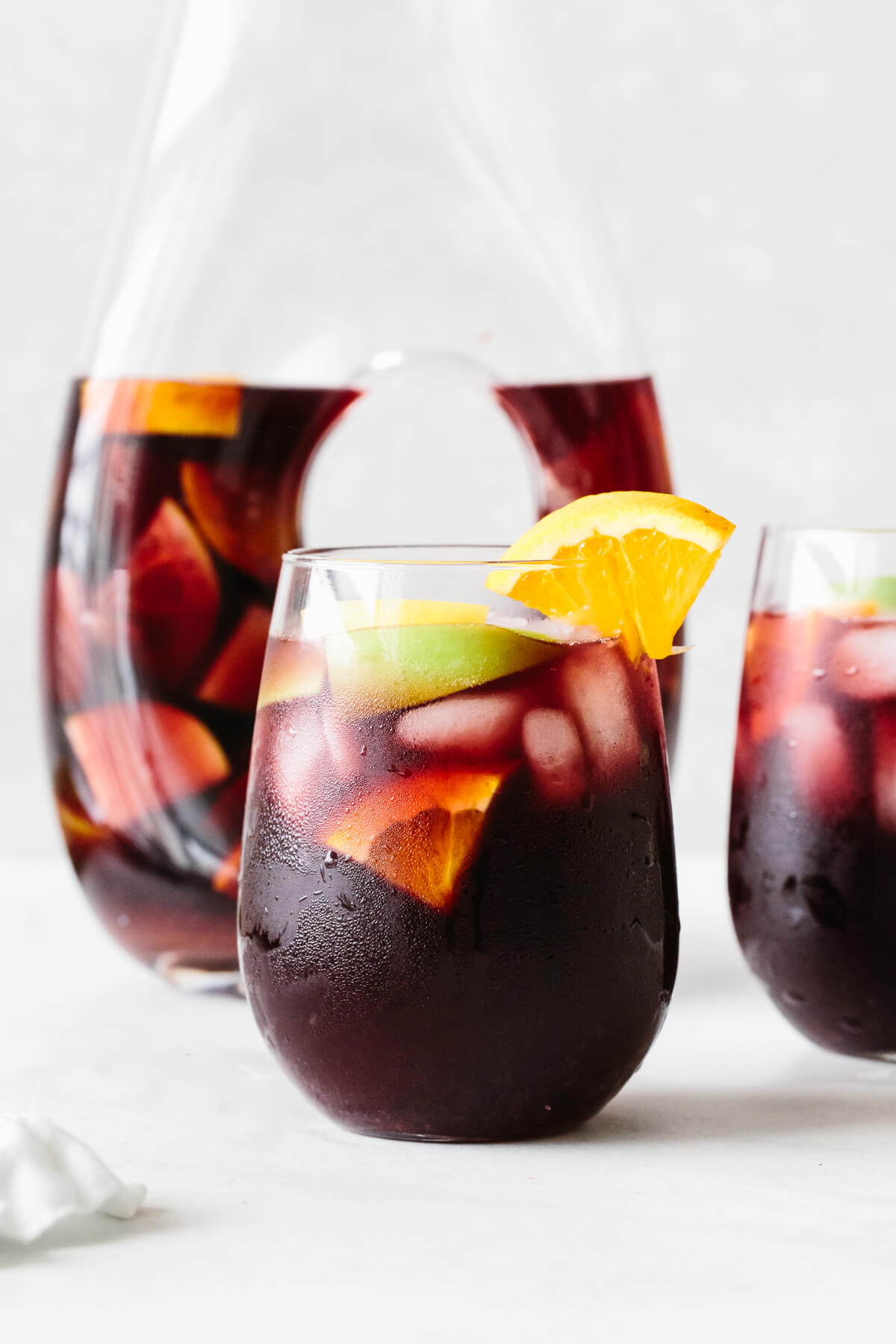 Red sangria in a glass with orange slice garnish and pitcher in the background.