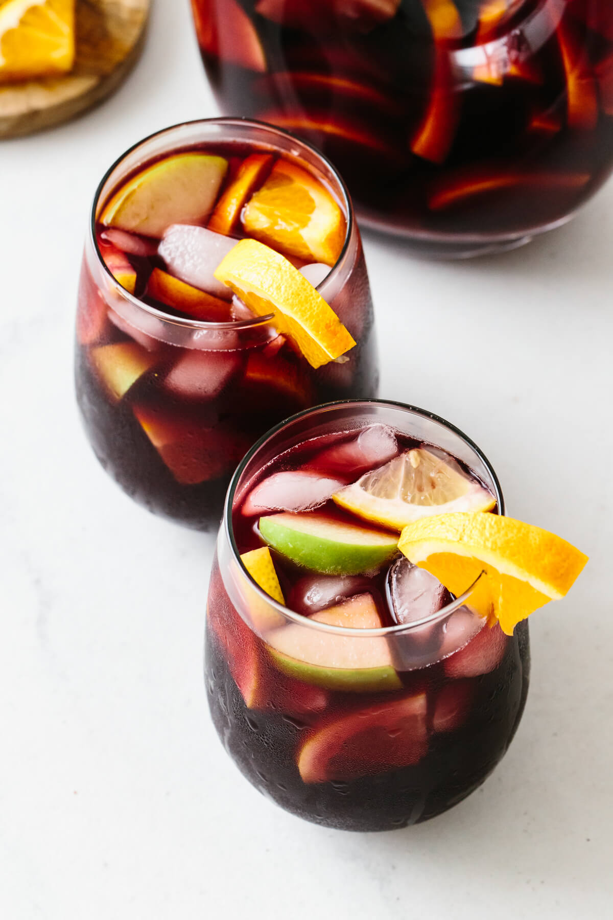 Two glasses of red sangria with orange garnishes.
