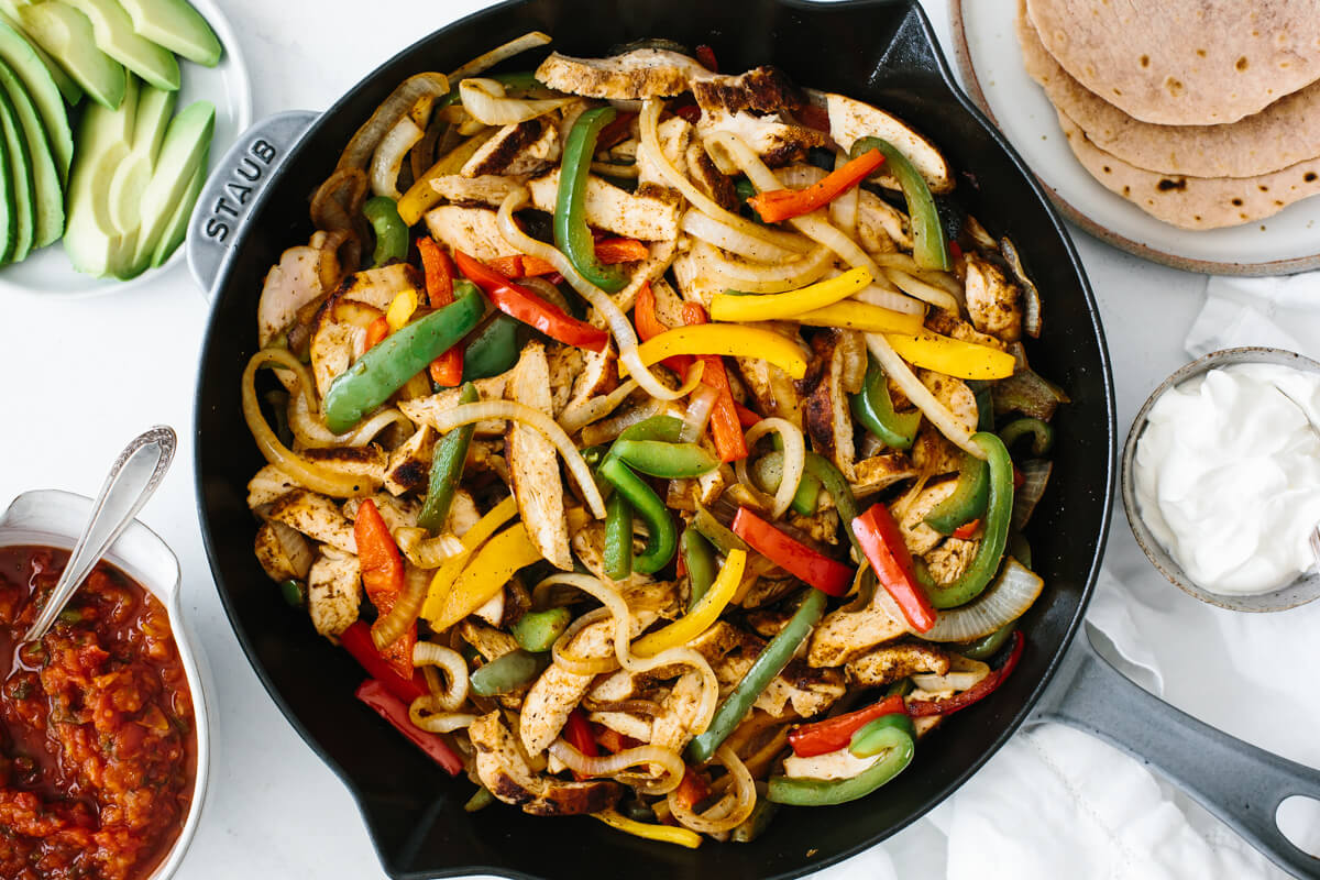 Chicken fajitas in a pan on a table with toppings for Cinco De Mayo