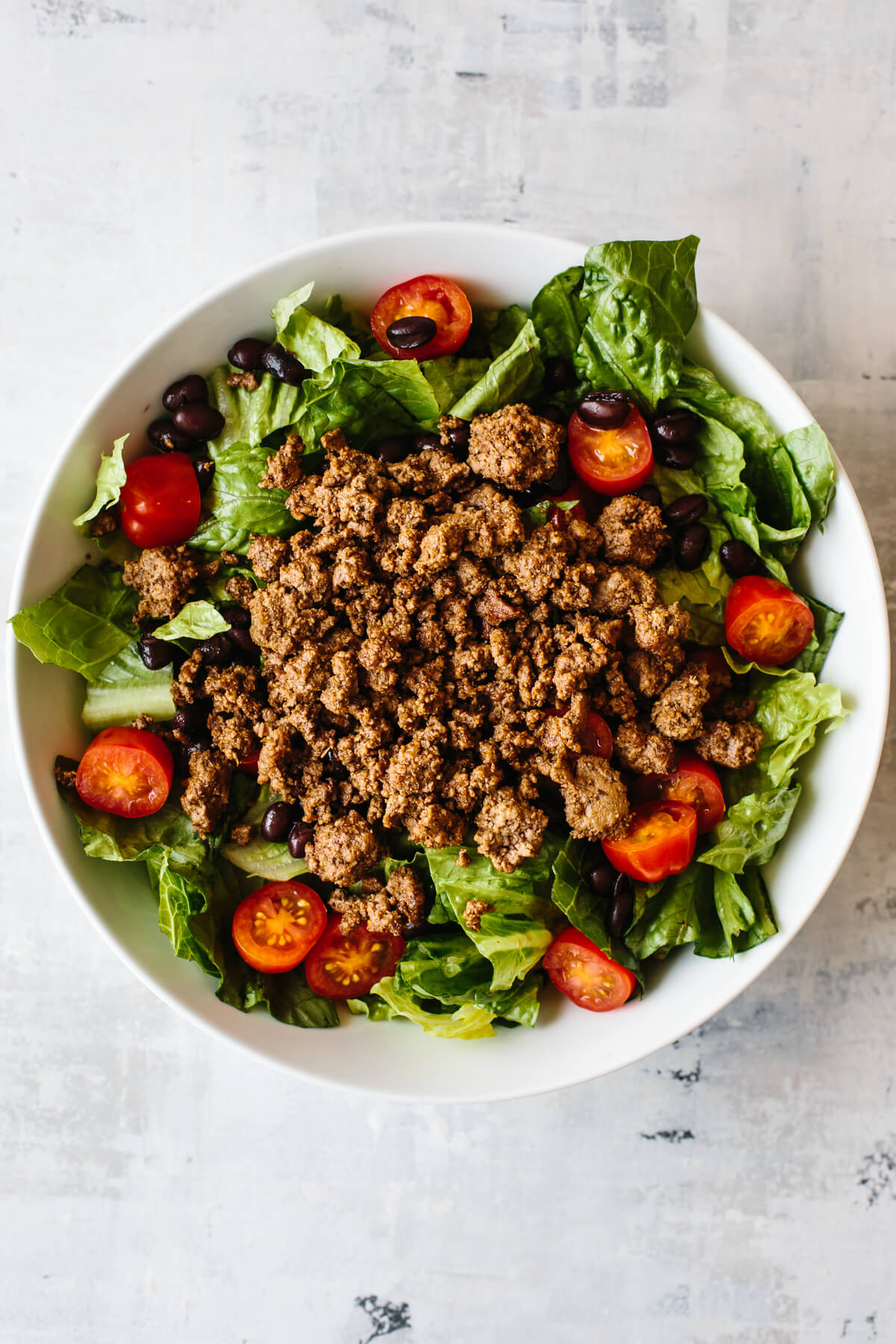 Bowl filled with lettuce, tomatoes, black beans and taco meat.