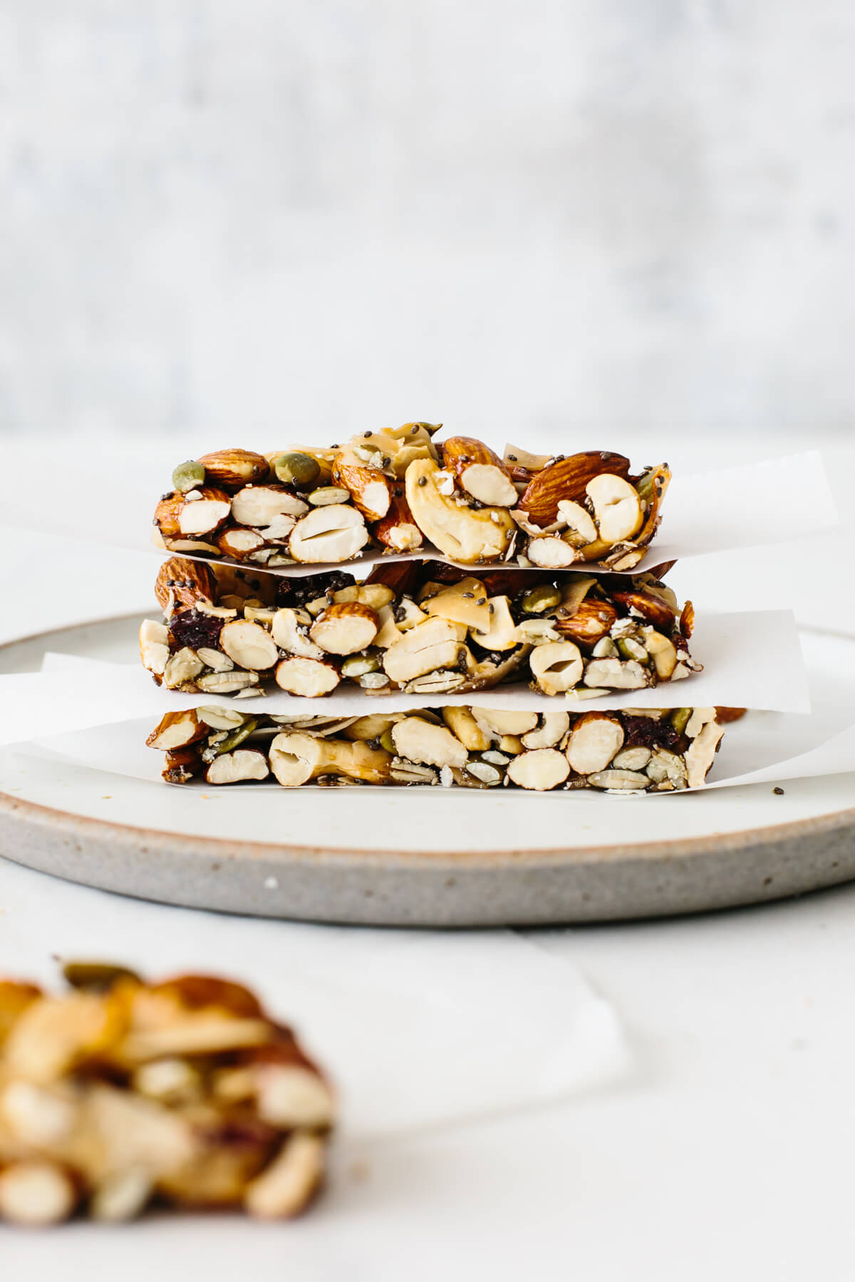 Three granola bars stacked on top of each other on a plate with parchment paper in between.