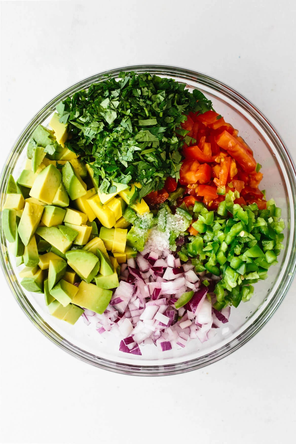 A mixing bowl with the ingredients to make avocado salsa.