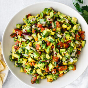 Avocado salsa in a bowl with tortilla chips on the side.