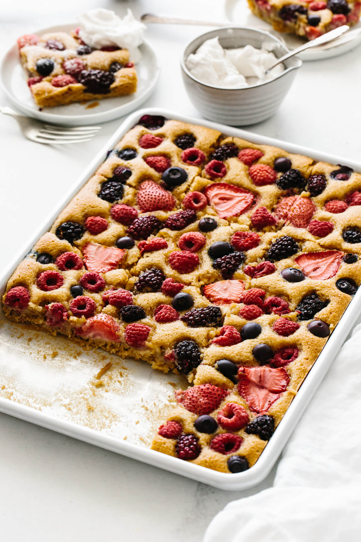 Sheet pan of berry cake with a few servings removed and on plates.