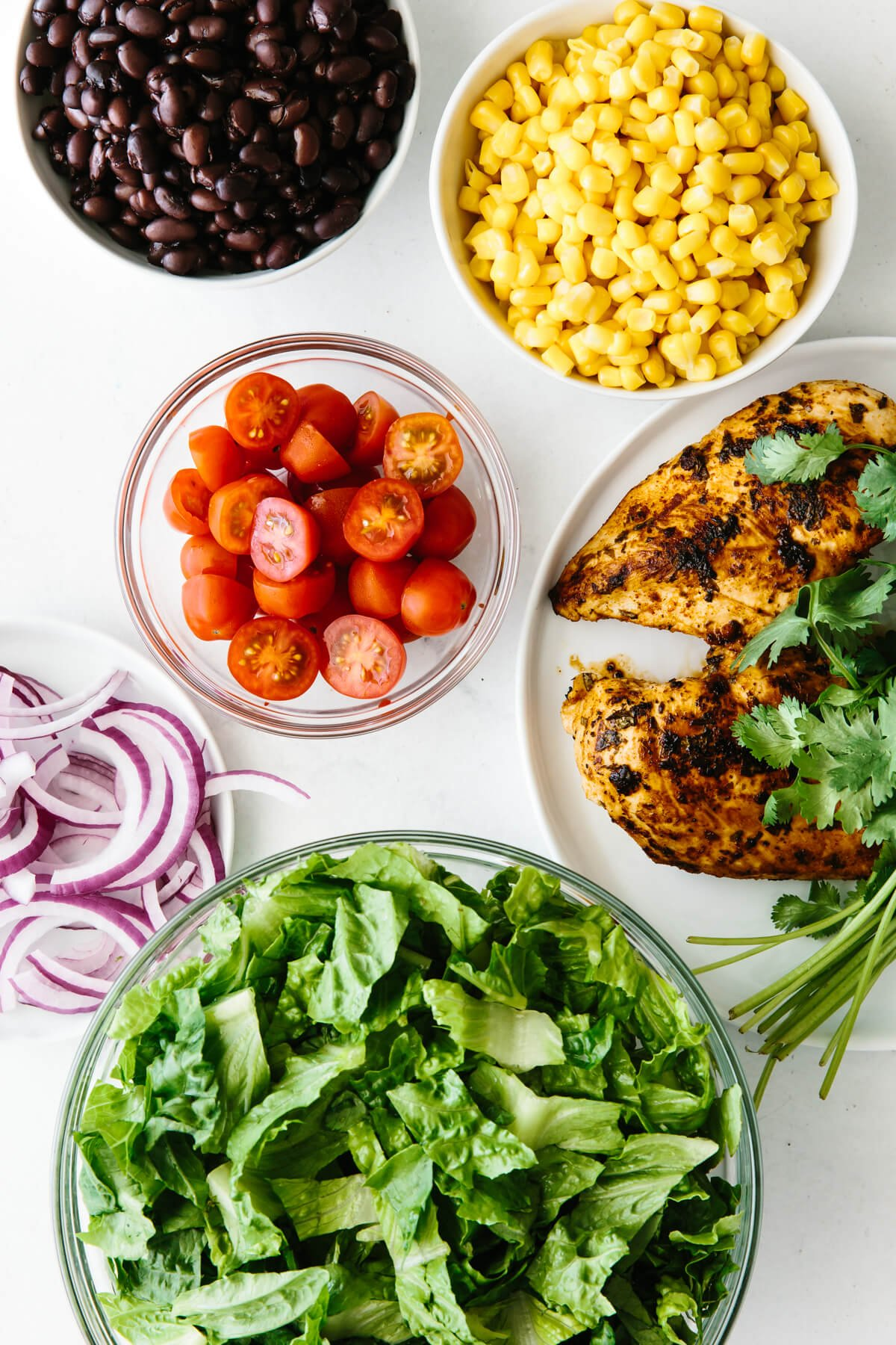 The ingredients to make southwestern chicken salad all in individual bowls.