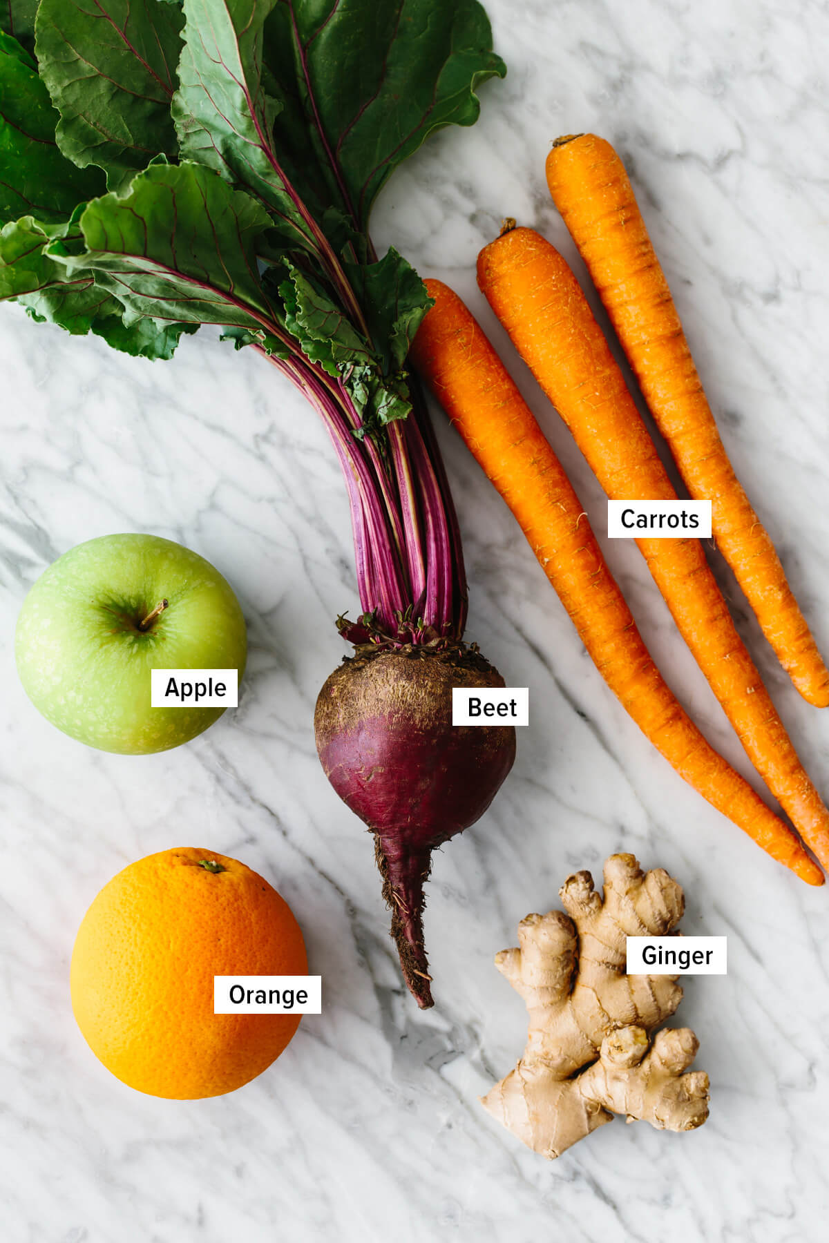 The ingredients to make the apple carrot beet smoothie on a kitchen countertop.