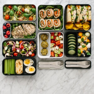 Several bento boxes on a table with different lunch recipes and ingredients.