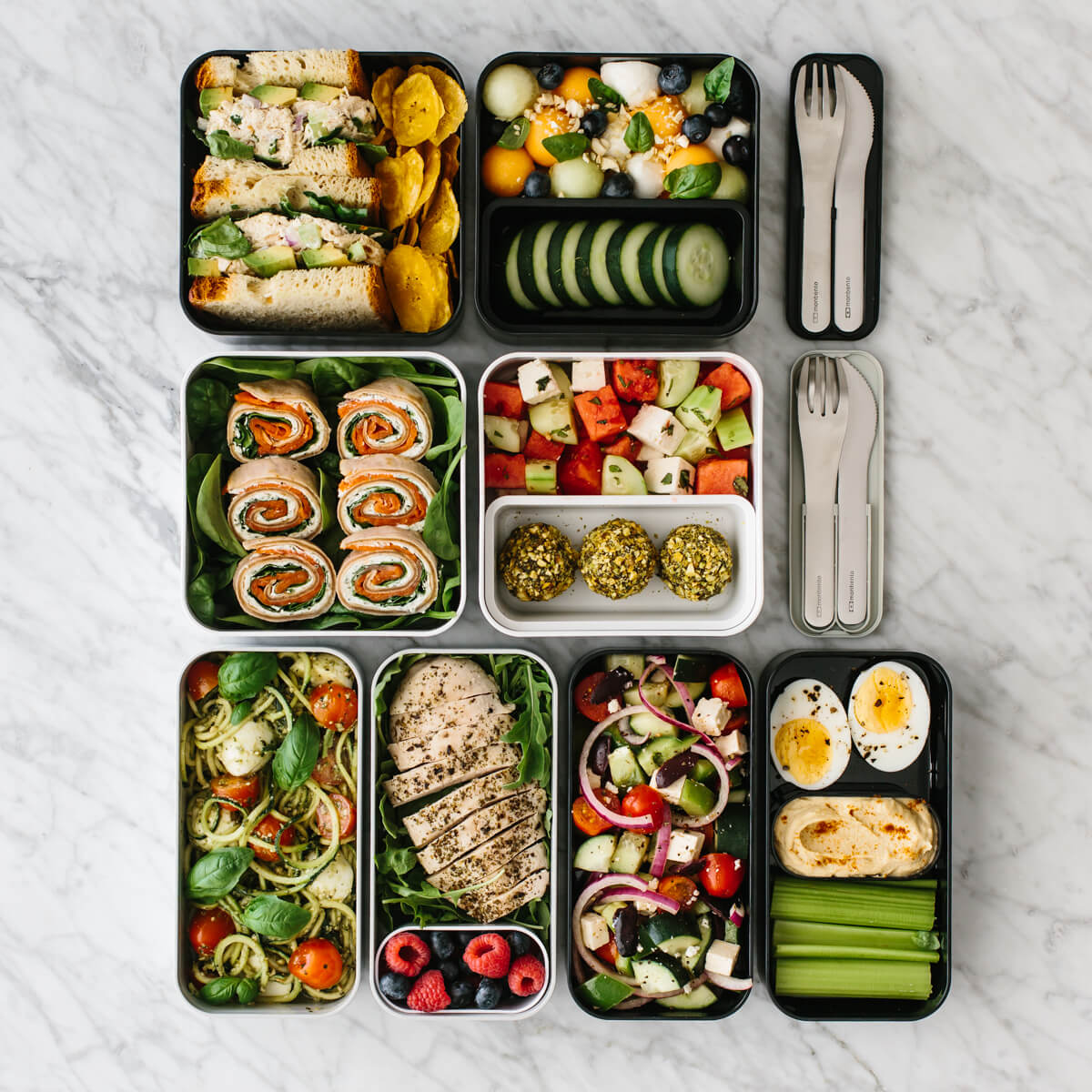 Several bento box lunches on a counter with cutlery.