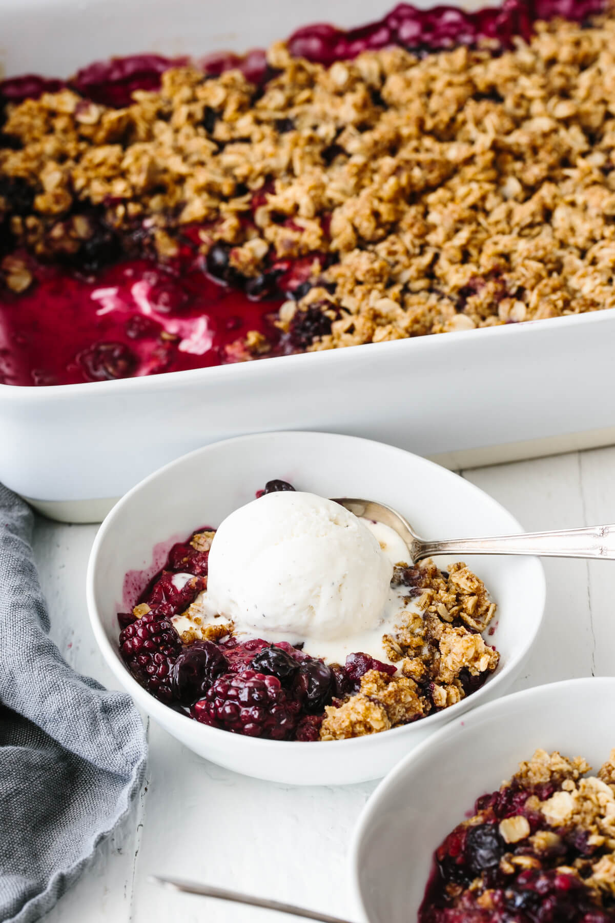 A bowl of berry crisp topped with ice cream.