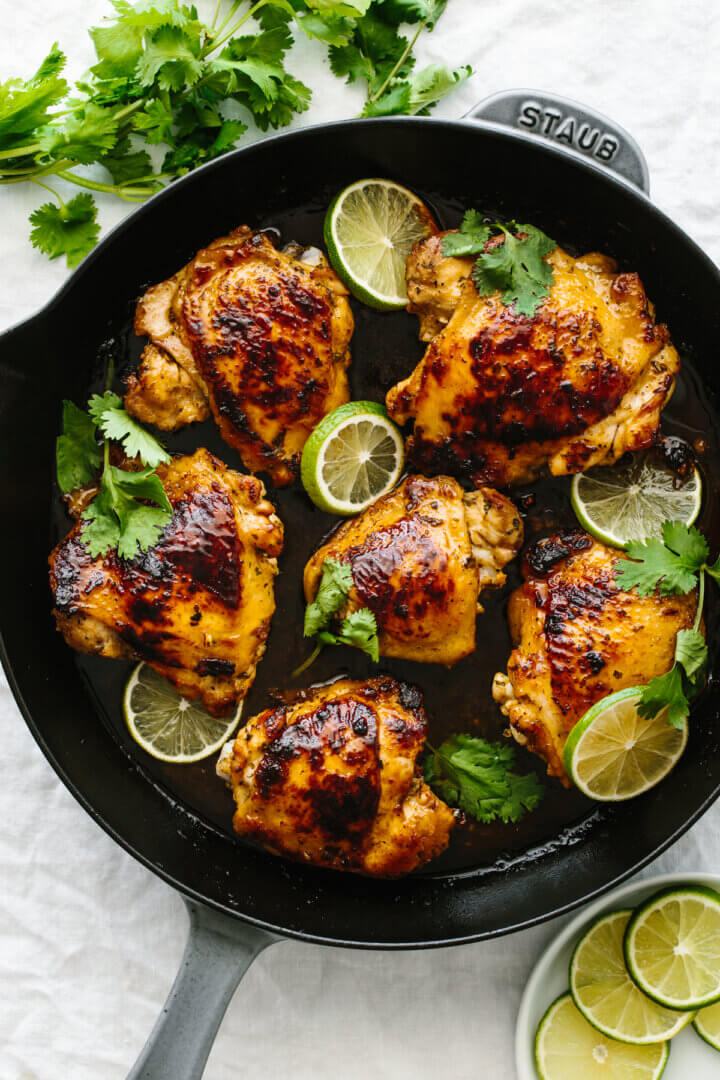 Six cooked chicken thighs with cilantro lime flavors in a fry pan.