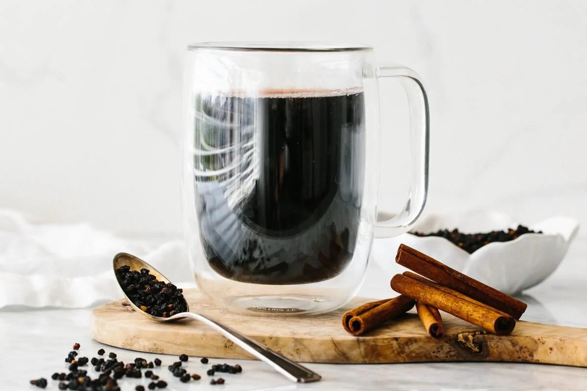 Elderberry tea in a glass next to dried elderberries and cinnamon.