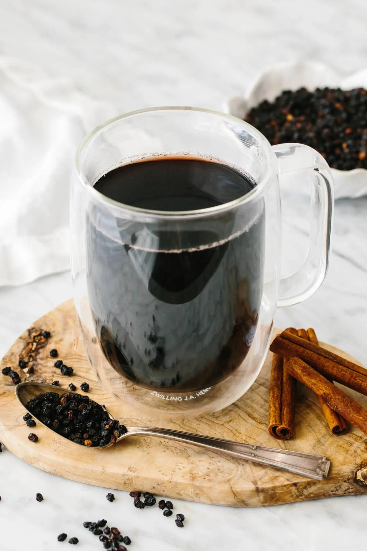 Elderberry tea in a glass next to dried elderberry and cinnamon sticks.