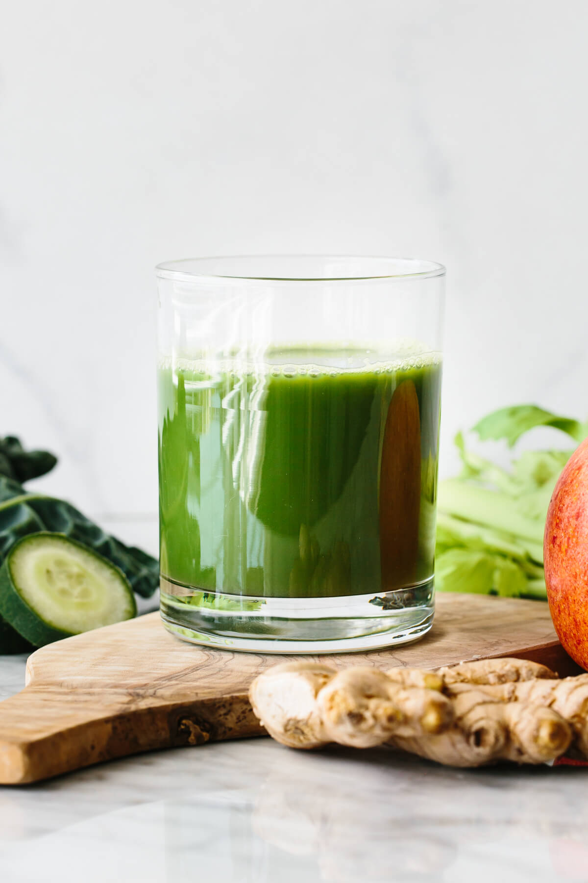 A glass of green juice, surrounded by vegetables.