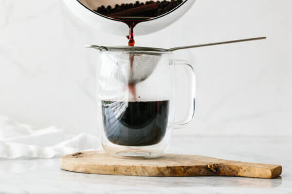 Straining the elderberry tea into a drinking glass.