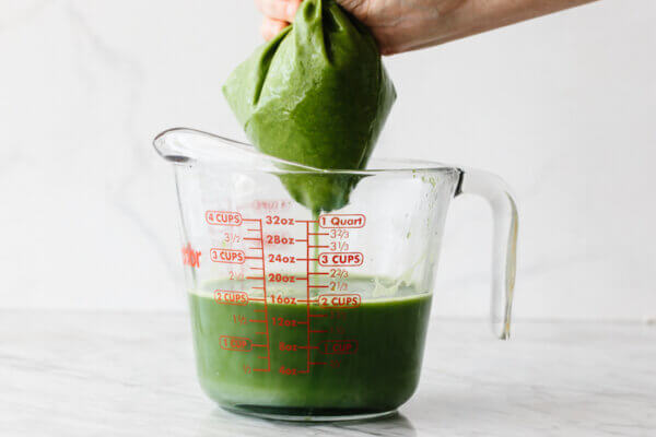 Squeezing green juice through a nut milk bag into a bowl, to strain it.