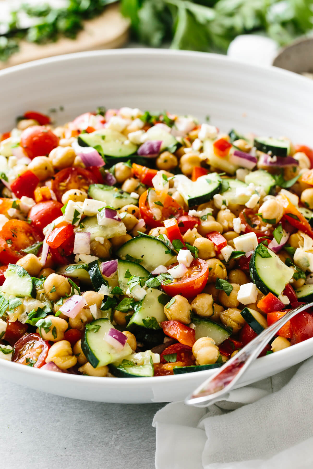 A bowl of Mediterranean chickpea salad with fresh parsley in the background.