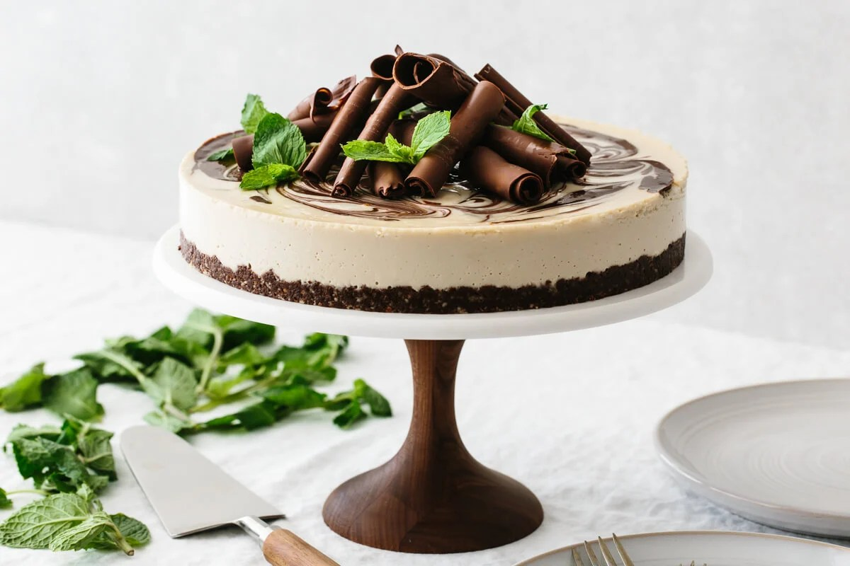 Adding toppings and garnish to the mint chocolate vegan cheesecake.