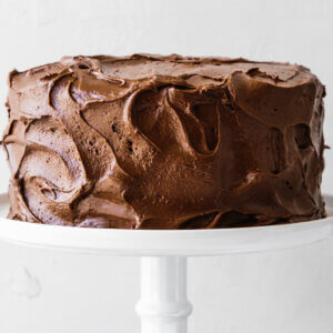 Paleo chocolate cake on a white cake stand.