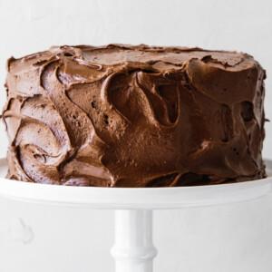 Paleo chocolate cake on a white cake stand.