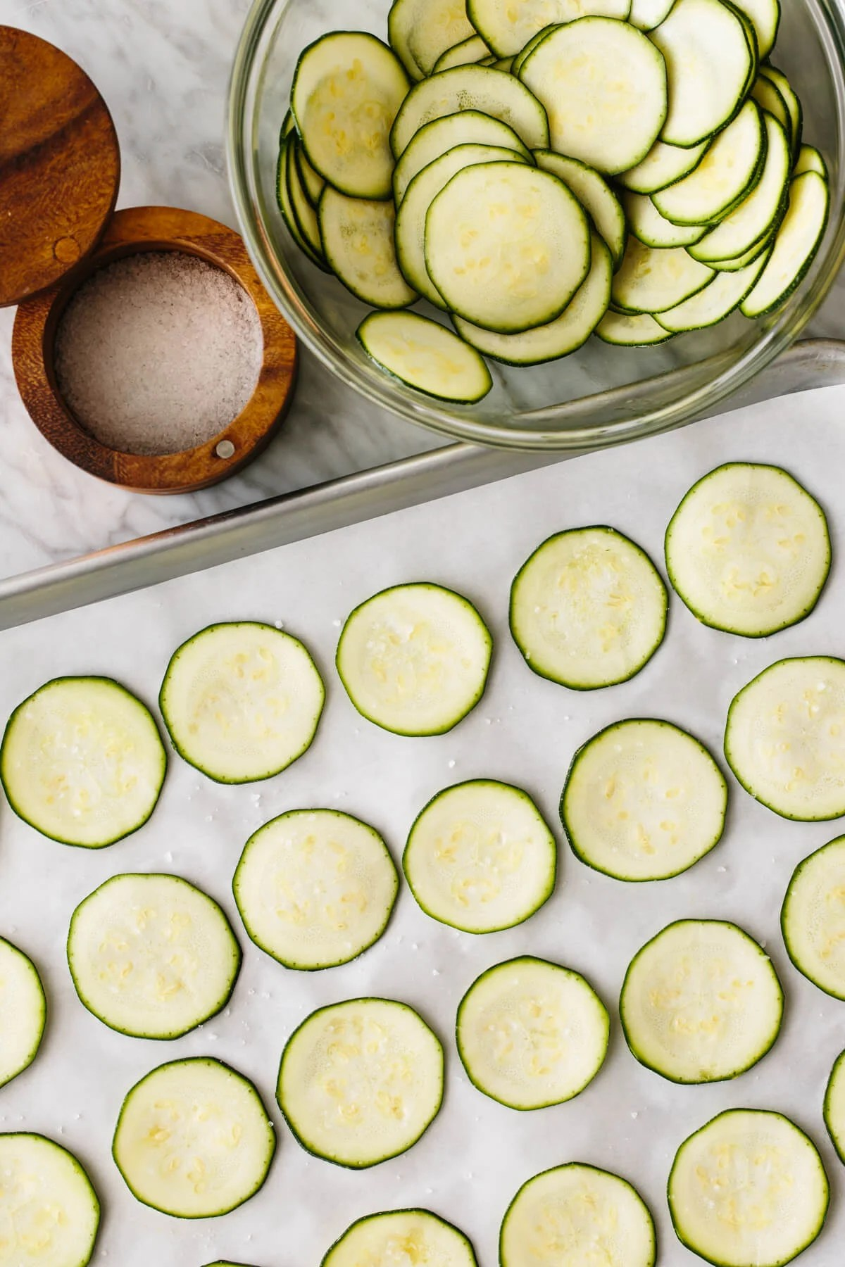 Fresh zucchini slices evenly laid out on a baking tray next to a wooden container with salt.