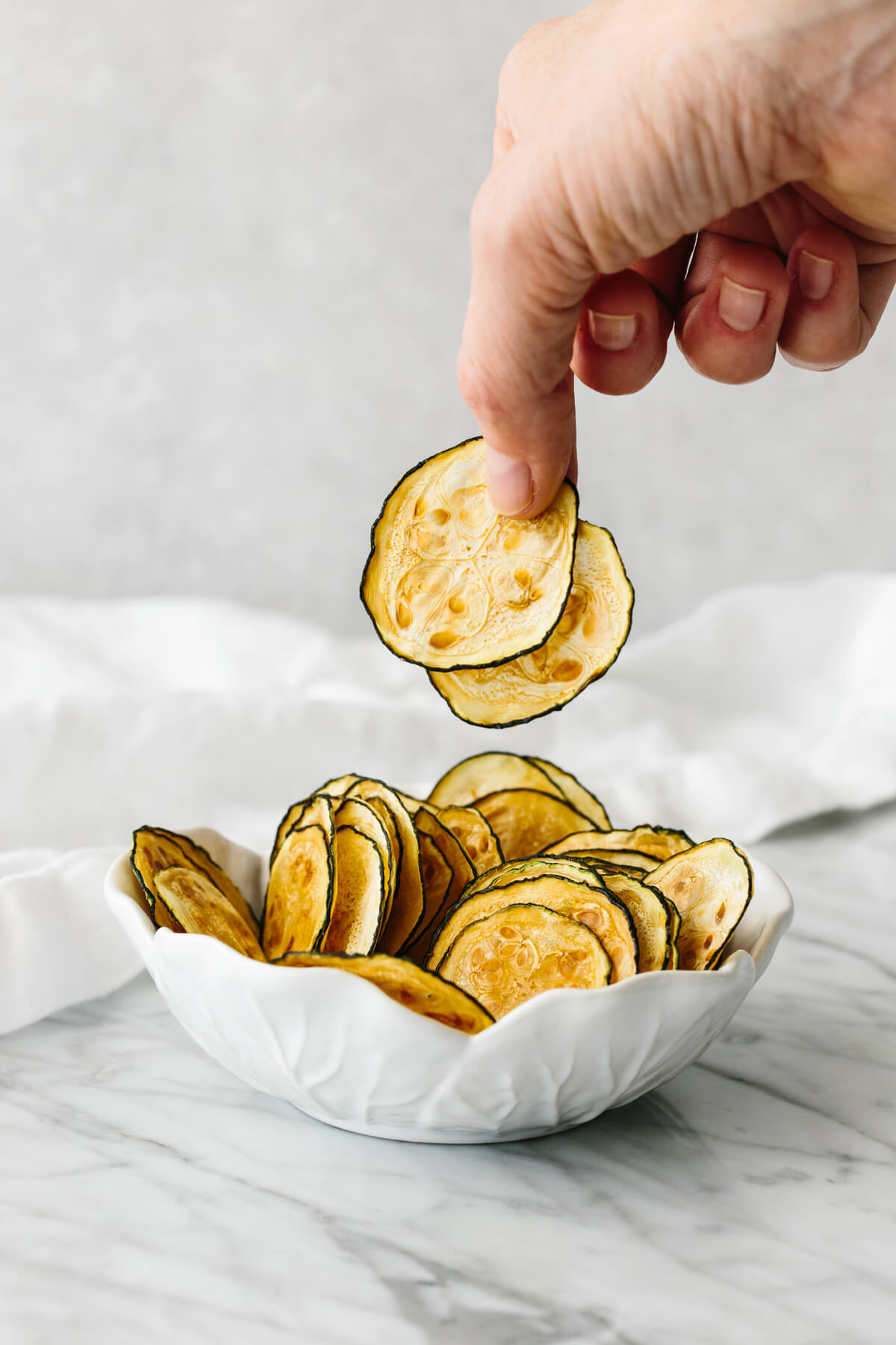 A hand picking up zucchini chips from a white bowl sitting on a table.